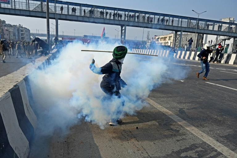 A farmer throws a tear gas shell back towards police in New Delhi