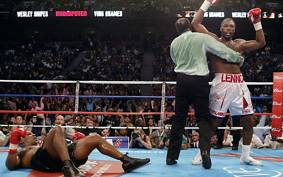 Heavyweight Champion Lennox Lewis of England (R) is held by referee Eddie Cotton after knocking downs challenger Mike Tyson of the US during the 4th round of their World Heavyweight Championship bout 08 June 2002 - AFP