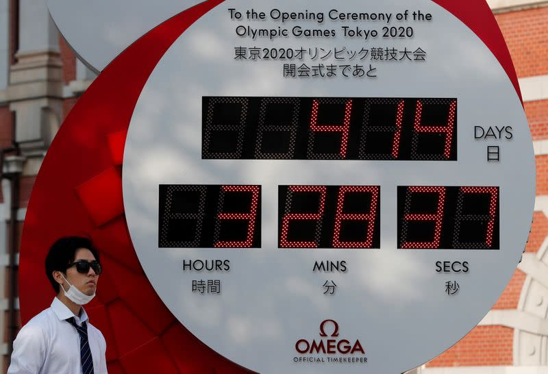 FILE PHOTO: A man wearing a protective mask walks past a countdown clock for the Tokyo 2020 Olympic Games amid the coronavirus disease (COVID-19) outbreak in Tokyo