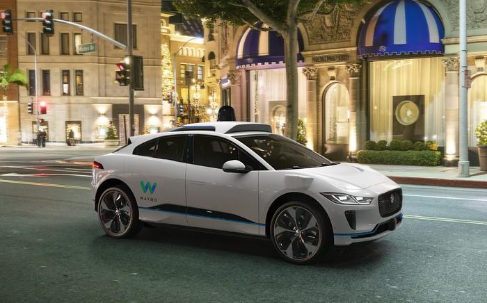 A white Jaguar I-Pace, an electric crossover SUV, with visible self-driving sensor hardware and Waymo logos, driving on a city street.