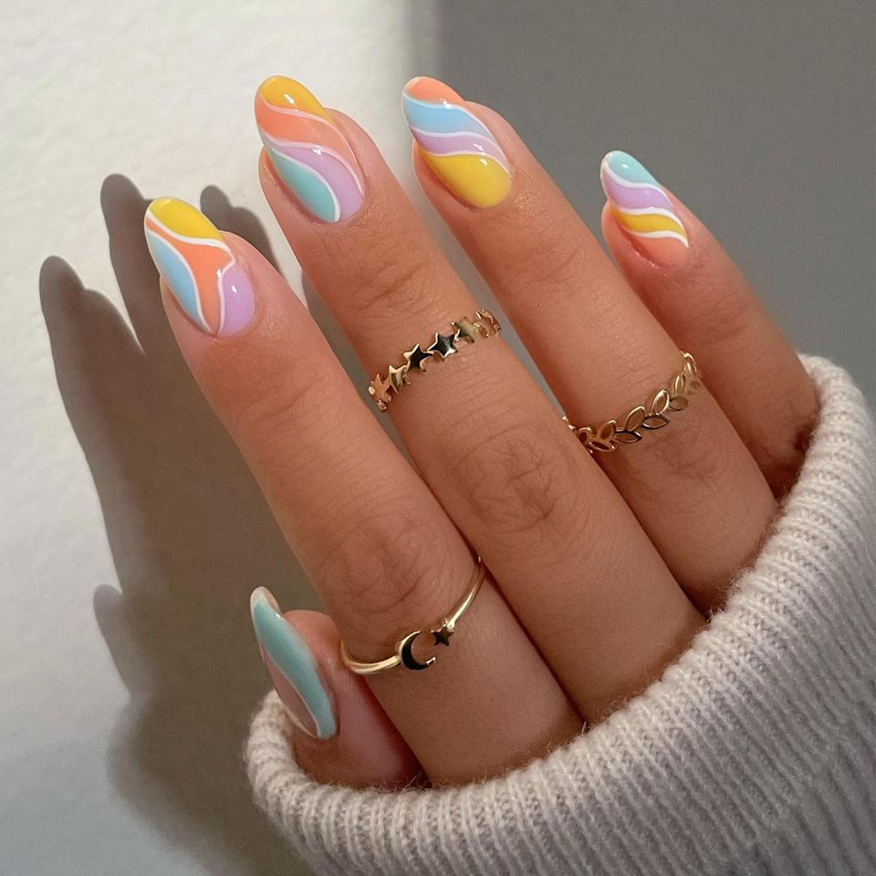"""<p>If you want to leave your swirls to a professional, this rainbow sherbert-esque set is your best bet for doing so. The multi-colored swirl style takes a bit more concentration, skill, and patience. Might as well let a nail artist who can create them in their sleep take the lead (while <a href=""""https://www.allure.com/story/covid-19-pandemic-effect-nail-salon-workers?mbid=synd_yahoo_rss"""" rel=""""nofollow noopener"""" target=""""_blank"""" data-ylk=""""slk:supporting a local business"""" class=""""link rapid-noclick-resp"""">supporting a local business</a>.) </p> <p>When arriving at your appointment, Le recommends giving your nail artist a couple of different versions of your favorite <a href=""""https://www.allure.com/gallery/best-spring-nail-designs?mbid=synd_yahoo_rss"""" rel=""""nofollow noopener"""" target=""""_blank"""" data-ylk=""""slk:swirl nail art"""" class=""""link rapid-noclick-resp"""">swirl nail art</a> — perhaps even all three of these <em>Allure</em> ones. """"I suggest not showing one photo and asking a nail artist to mimic just that because that's when the nail art gets tricky for the artist,"""" she explains. """"Tell them what you like, pick out a few of your <a href=""""https://www.allure.com/gallery/summer-nail-polish-colors?mbid=synd_yahoo_rss"""" rel=""""nofollow noopener"""" target=""""_blank"""" data-ylk=""""slk:favorite colors"""" class=""""link rapid-noclick-resp"""">favorite colors</a>, and let the artist do what they do best.""""</p>"""