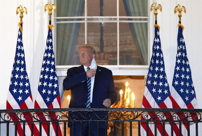 U.S. President Donald Trump removes his mask upon return to the White House from Walter Reed National Military Medical Center on October 5, 2020 in Washington, DC. Trump spent three days hospitalized for coronavirus.