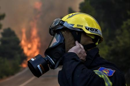 A firefighter adjusts his mask as a wildfire burns at the village of Kontodespoti, on the island of Evia