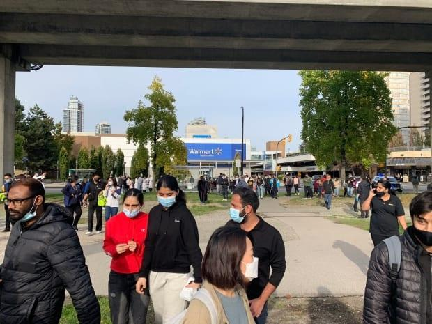 A crowd outside Metrotown after the mall was evacuated Friday afternoon due to a police incident. (Jon Hernandez/CBC - image credit)