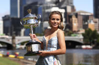 FILE - In this Sunday, Feb. 2, 2020 file photo, United States' Sofia Kenin holds the Daphne Akhurst Memorial Cup at a photo shoot on the Yarra River following her win over Spain's Garbine Muguruza in women's singles final of the Australian Open tennis championship in Melbourne, Australia. Australian Open starts the 2021 Grand Slam tennis season on Monday, Feb. 8, 2021 in Melbourne (Sunday in the United States), with a delay of three weeks because of the coronavirus pandemic. (AP Photo/Dita Alangkara, File)