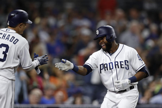 San Diego Padres' Manuel Margot, right, is greeted by teammate Manny Machado after hitting a home run during the fifth inning of a baseball game against the Chicago Cubs on Wednesday, Sept. 11, 2019, in San Diego. (AP Photo/Gregory Bull)