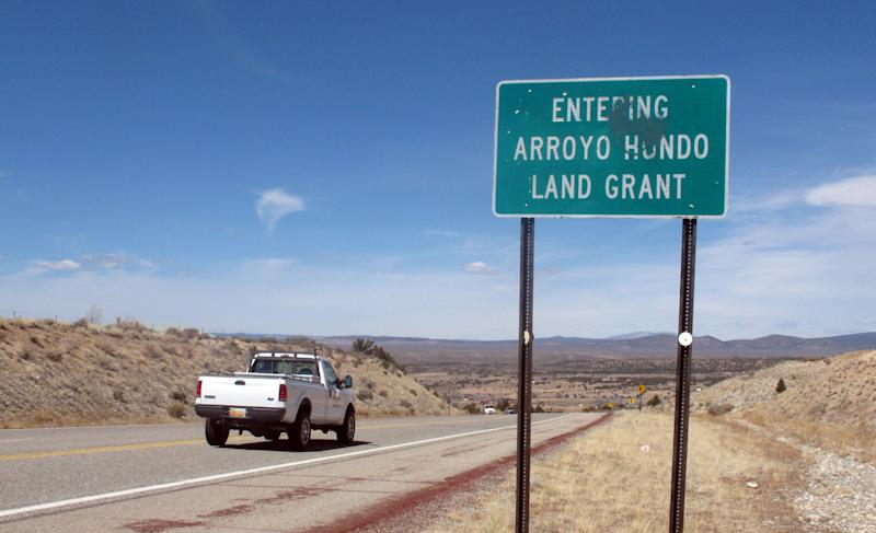 In this March 26, 2013 photo, the sign of the Arroyo Hondo Land Grant is shown at the entrance of the historical northern New Mexico Spanish land grant. Heirs and homeowners currently are locked in a dispute after a land grant board filed a warranty deed in an attempt to reclaim 20,000 acres of private land originally granted by Spain's colonial government to Arroyo Hondo's founding families. The fight is preventing homeowners from selling property, refinancing mortgages, or getting insurance policies while the courts struggle to unravel the conflict. (AP Photo/Russell Contreras)