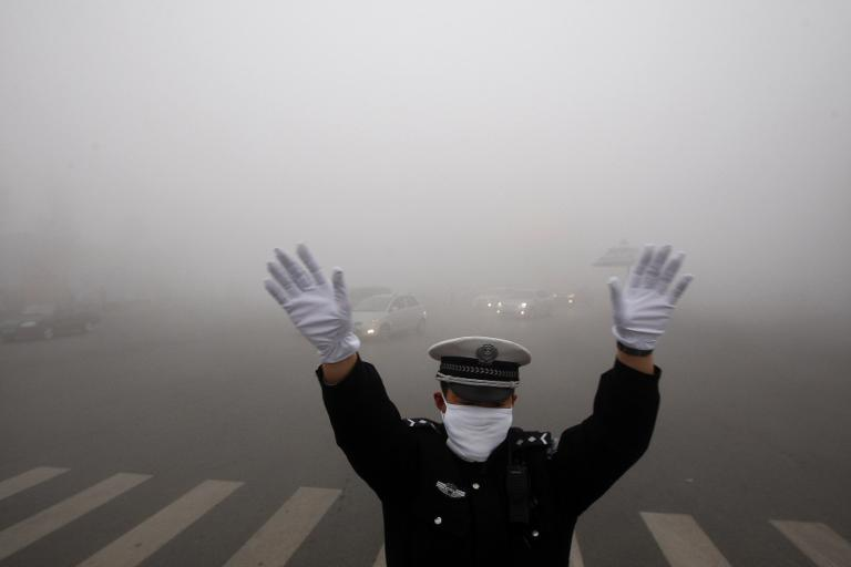 A policeman is seen on a street in heavy smog in Harbin, northeast China's Heilongjiang province, on October 21, 2013