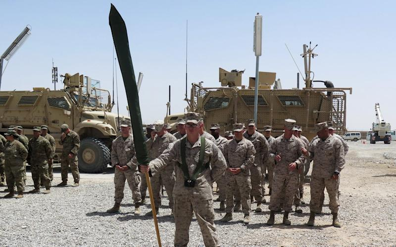 US Marines stand at attention during a transfer of authority ceremony at Shorab camp, in Helmand province - REUTERS