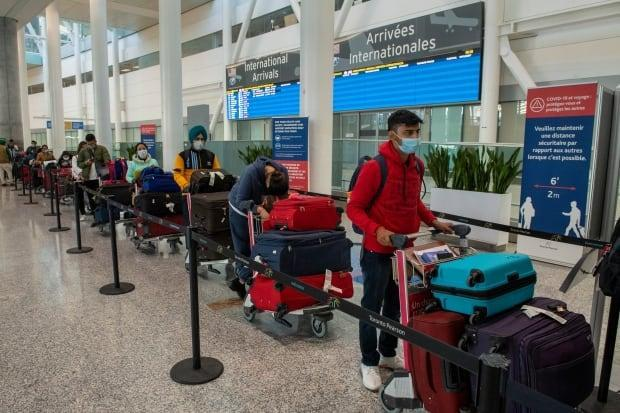 Passengers from New Delhi wait in long lines for transportation to their quarantine hotels at Pearson Airport in Toronto on Friday April 23, 2021. Canada's ArriveCan app, which allows travellers to register their arrival at the hotels, could be augmented to contain personal vaccine information, said Health Minister Patty Hajdu. (Canadian Press/Frank Gunn - image credit)