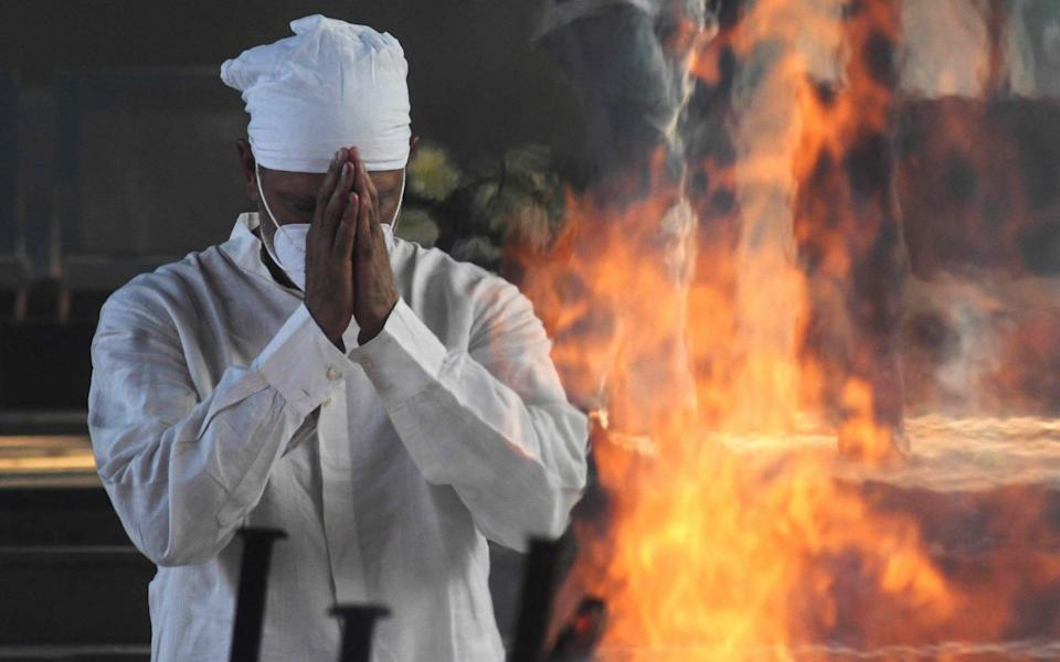 Jeev Milkha offer prayers in front of the funeral pyre of his 91-year-old father Milkha Singh who died from Covid-19 - AP