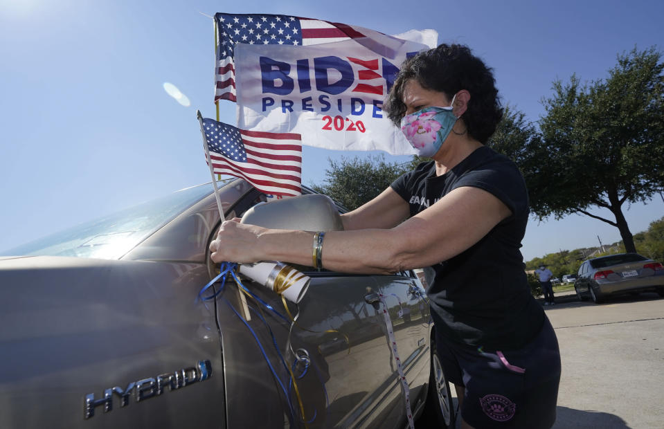 Ann Grannan puts a flag on her car before a Ridin' With Biden event Sunday, Oct. 11, 2020, in Plano, Texas. Democrats in Texas are pressing Joe Biden to make a harder run at Texas with less than three weeks until Election Day. (AP Photo/LM Otero)