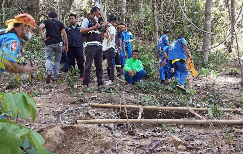 Rescue workers and forensic officials inspect the site of a mass grave uncovered at an abandoned jungle camp in the Sadao district of Thailand's southern Songkhla province bordering Malaysia on May 1, 2015 (AFP Photo/)