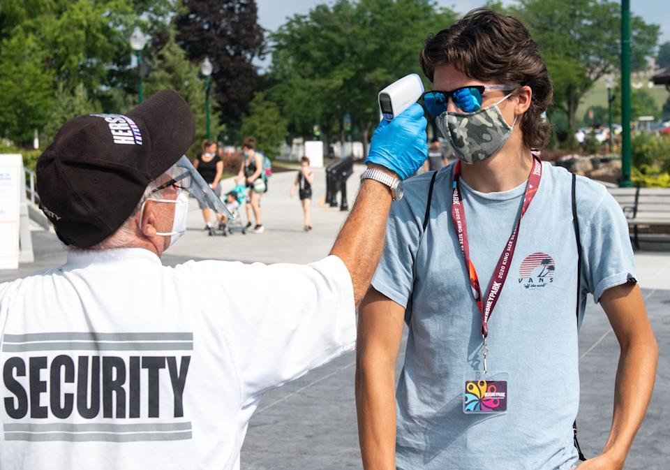 A security person greets visitors with a non-contact temperature reader before entering the park. No one is admitted with aÊtemperature of 100.3 or higher, July 9, 2020.