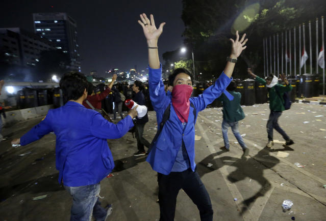 Student protesters shout slogan during a protest outside the parliament in Jakarta, Indonesia Tuesday, Sept. 24, 2019. Police fired tear gas and water cannons Tuesday to disperse thousands of rock-throwing students protesting a new law that they said has crippled Indonesia's anti-corruption agency.(AP Photo/Achmad Ibrahim)