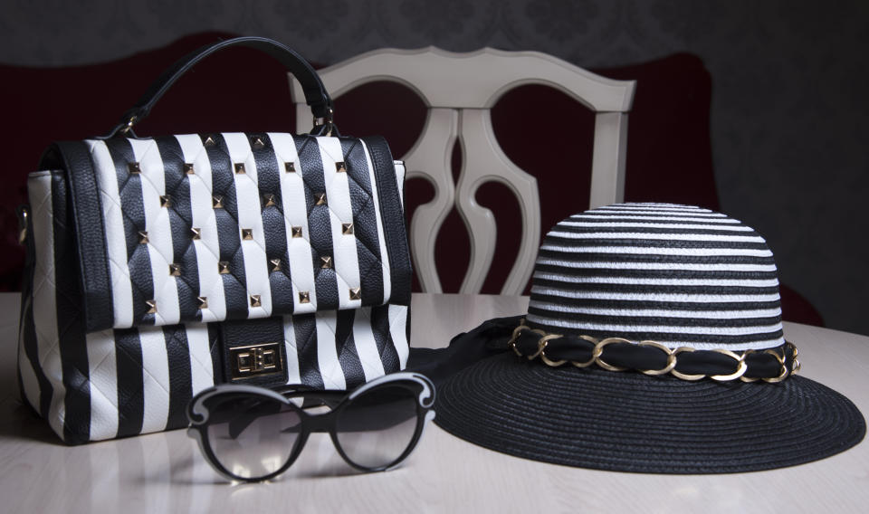 Striped women's hat, black and white purse with stripes and sunglasses on table. Modern fashion style