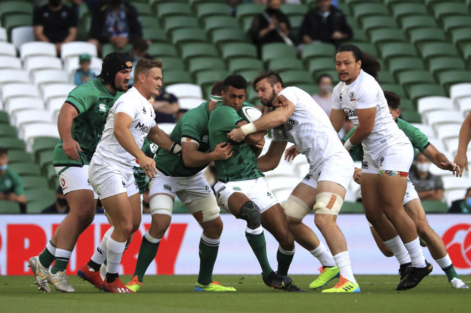 Ireland's Robert Baloucoune, centre, on the attack as he makes his debut, during the Rugby Union International Summer Series match between Ireland and USA, in Dublin, Ireland, Saturday July 10, 2021. (Donall Farmer/PA via AP)
