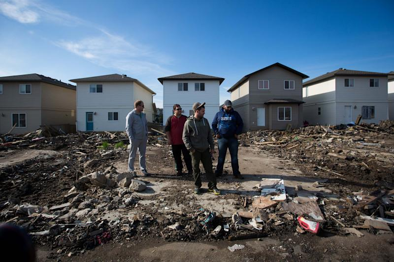 FILE PHOTO - Residents look over the damage in the Timberlea neighbourhood as thousands of evacuees who fled a massive wildfire begin to trickle back to their homes in Fort McMurray, Alberta, Canada on June 2, 2016. REUTERS/Topher Seguin/File Photo