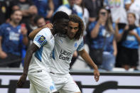 Marseille's Bamba Dieng, left, celebrates with his teammate Marseille's Matteo Guendouzi after scoring his side's opening goal during the French League One soccer match between Marseille and Rennes at the Velodrome stadium in Marseille, France, Sunday, Sept. 19, 2021. (AP Photo/Daniel Cole)