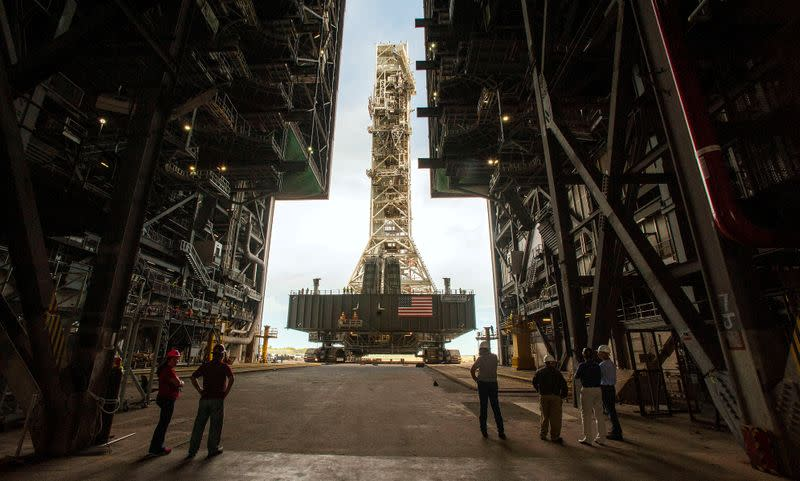 FILE PHOTO: NASA employees look on as the Artemis launch tower rolls back from Pad 39B inside Bay 3 of the Vehicle Assembly Building at the Kennedy Space Center before Hurricane Dorian makes landfall