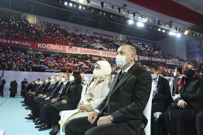 Turkey's President Recep Tayyip Erdogan sits with his wife Emine at a rally of his ruling party's congress inside a packed sports hall in Ankara, Turkey, Wednesday, March 24, 2021. Erdogan has come in the firing line for holding the rally inside the closed venue amid a new surge in COVID-19 cases. Thousands of party supporters filled the stands of the 10,400-capacity sports hall in the capital, in disregard of the government's own social distancing rules to fight the coronavirus pandemic. (Turkish Presidency via AP, Pool)