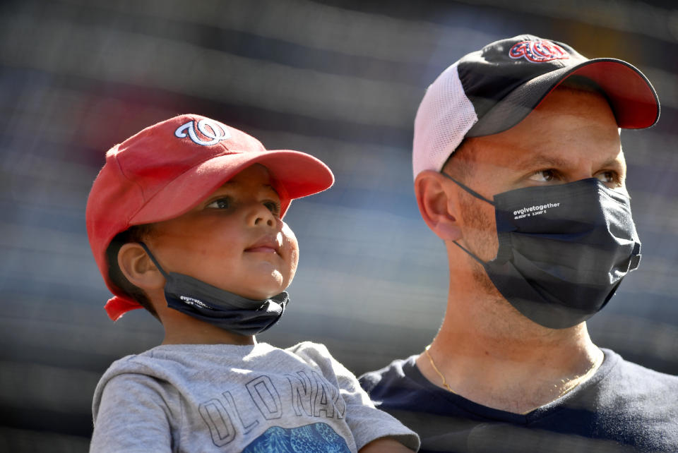 Watching a baseball game wearing face masks. (Randy Litzinger/Icon Sportswire via Getty Images)