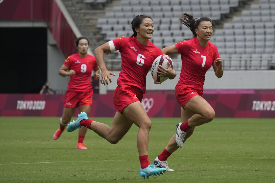 China's Wang Wanyu, center, trailed by teammates Chen Keyi, right, and Yang Feifei, runs on her way to score a try in their women's rugby sevens match at the 2020 Summer Olympics, Friday, July 30, 2021 in Tokyo, Japan. (AP Photo/Shuji Kajiyama)