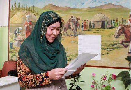 A woman studies her ballot at a polling station during the presidential election in the village of Kyzyl-Birdik, Kyrgyzstan October 15, 2017. REUTERS/Vladimir Pirogov