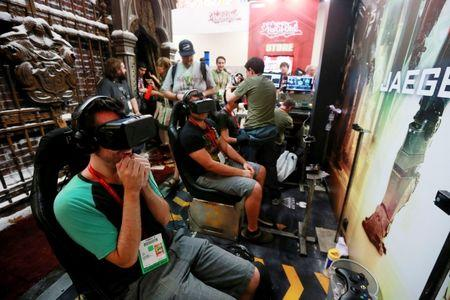 """Attendees wearing Oculus Rift virtual reality headsets view a 3D video for """"Pacific Rim: Jaeger Pilot"""" during the 2014 Comic-Con International Convention in San Diego"""