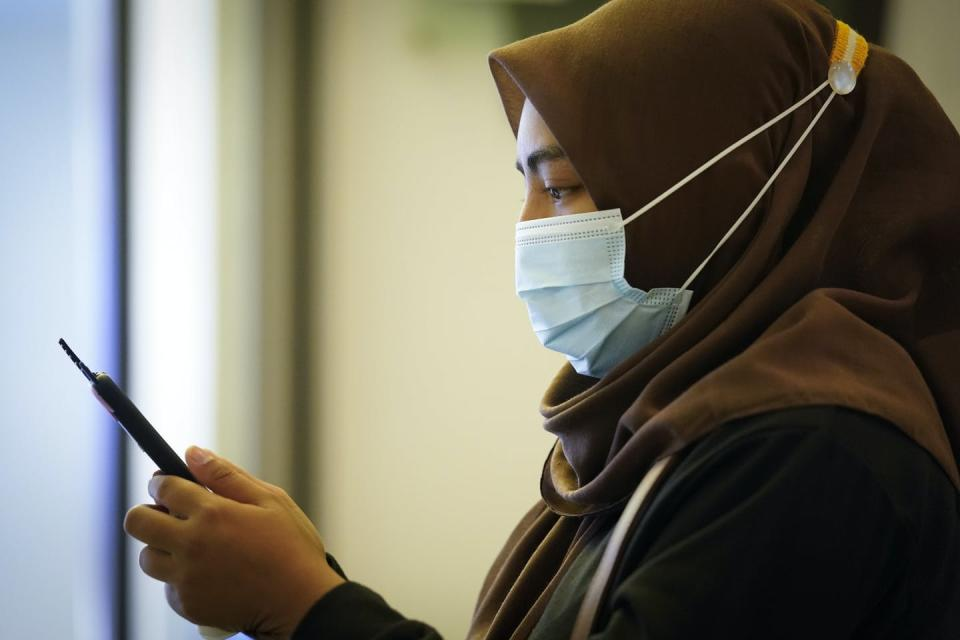 A woman wearing a mask looks at her phone