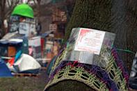 A sign is seen on a tree at a makeshift camp where Extinction Rebellion activists demonstrate as others occupy tunnels under Euston Square Gardens, to protest against the HS2 high-speed railway in London, Britain, January 27, 2021. REUTERS/Hannah McKay