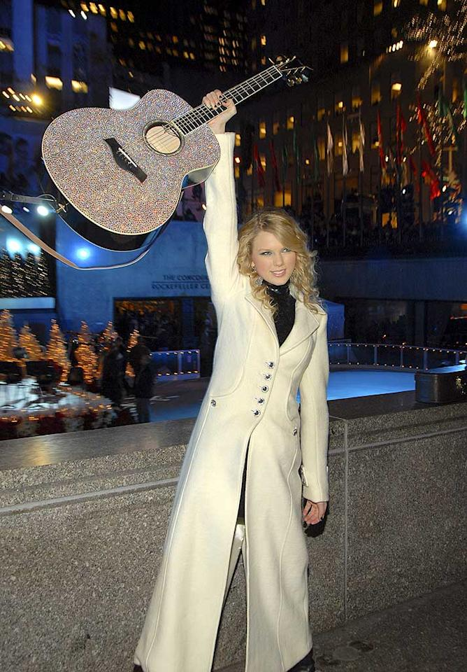 "Country cutie Taylor Swift shows of her glittery guitar. Kevin Mazur/<a href=""http://www.wireimage.com"" target=""new"">WireImage.com</a> - November 28, 2007"