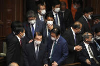 Lawmakers walk in an extraordinary Diet session at the lower house of parliament before the lower house was dissolved, Thursday, Oct. 14, 2021, in Tokyo. Japan's new Prime Minister Fumio Kishida dissolved the lower house of parliament Thursday, paving the way for Oct. 31 national elections.(AP Photo/Eugene Hoshiko)