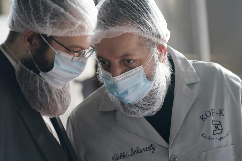 Rabbis Joseph Schwartz, right, and Mendel Einhorn confer as they supervise Hanan Products preparations for their kosher-for-passover production run, Thursday, Jan. 7, 2021, in Hicksville, N.Y. The rabbis are tasked with ensuring that the production line and foods made here meet the strict kosher requirements of Passover. (AP Photo/Seth Wenig)