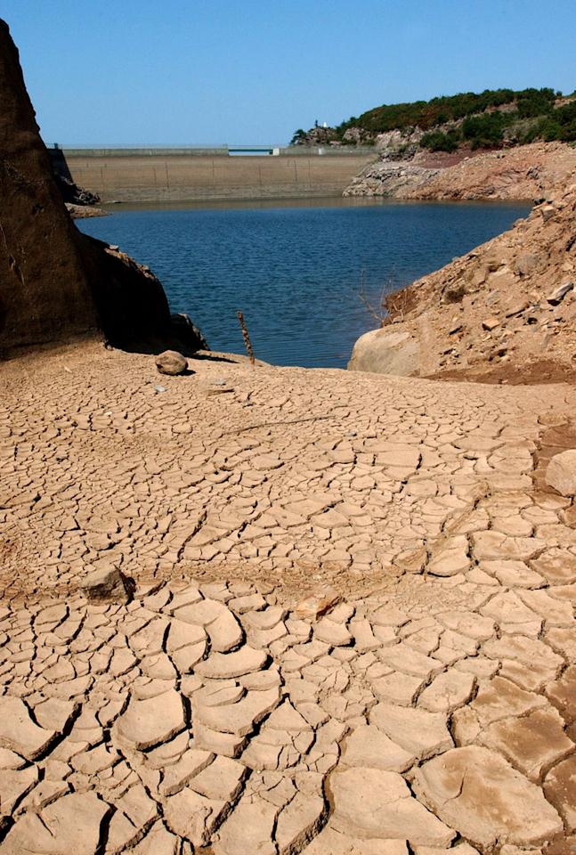 FILE - In this Aug. 19, 2003 file photo, the Ibardin lake, which provides drinking water to the southern French cities of Hendaye, Biriatu and Urrugne, is almost dry due to the recent heat wave, near the French-Spanish border. The relentless, weather-gone-crazy type of heat that has blistered the United States and other parts of the world in recent years is so rare and off-the-charts that it can't be anything but man-made global warming, a new statistical analysis from a top government scientist says. (AP Photo/Bob Edme, File)