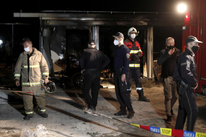 Firemen and police officers stand near a burned out makeshift hospital in North Macedonia's northwestern town of Tetovo, early Thursday, Sept. 9, 2021. The blaze occurred late Wednesday at the makeshift hospital for COVID-19 patients in Tetovo. (AP Photo/Boris Grdanoski)