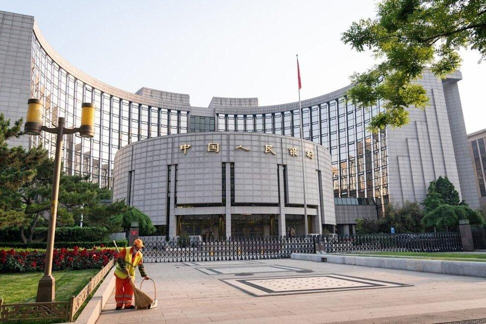 A cleaner sweeps the ground in front of the People's Bank of China headquarters in Beijing. Photo: Bloomberg