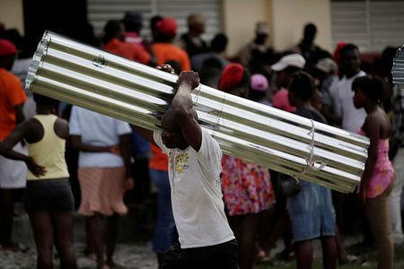 A man carries a metal sheet during the eviction of residents from a shelter for people displaced by Hurricane Matthew in Lycee Jean Claude Museau, which will be used as a voting centre, before the election in Les Cayes, Haiti, November 19, 2016. REUTERS/Andres Martinez Casares