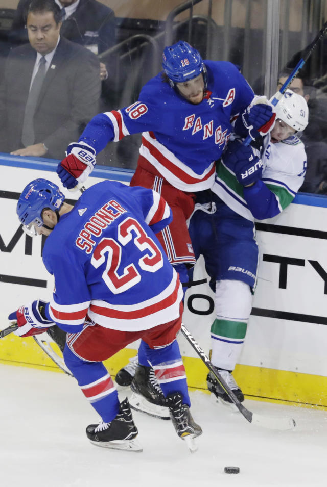 New York Rangers' Marc Staal (18) checks Vancouver Canucks' Troy Stecher (51) as Ryan Spooner (23) skates fights for control of the puck during the third period of an NHL hockey game Monday, Nov. 12, 2018, in New York. The Rangers won 2-1. (AP Photo/Frank Franklin II)