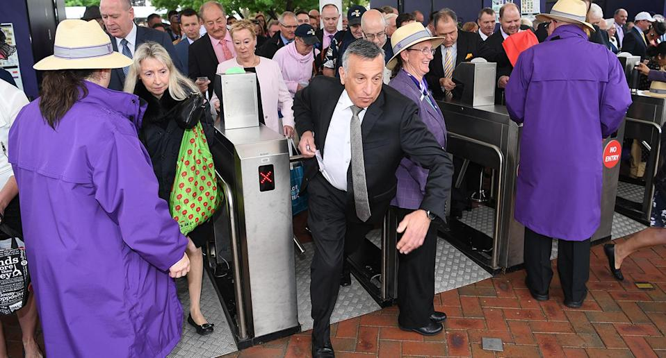 They're off … Racegoers run through the entry gates at Flemington. Image: AAP
