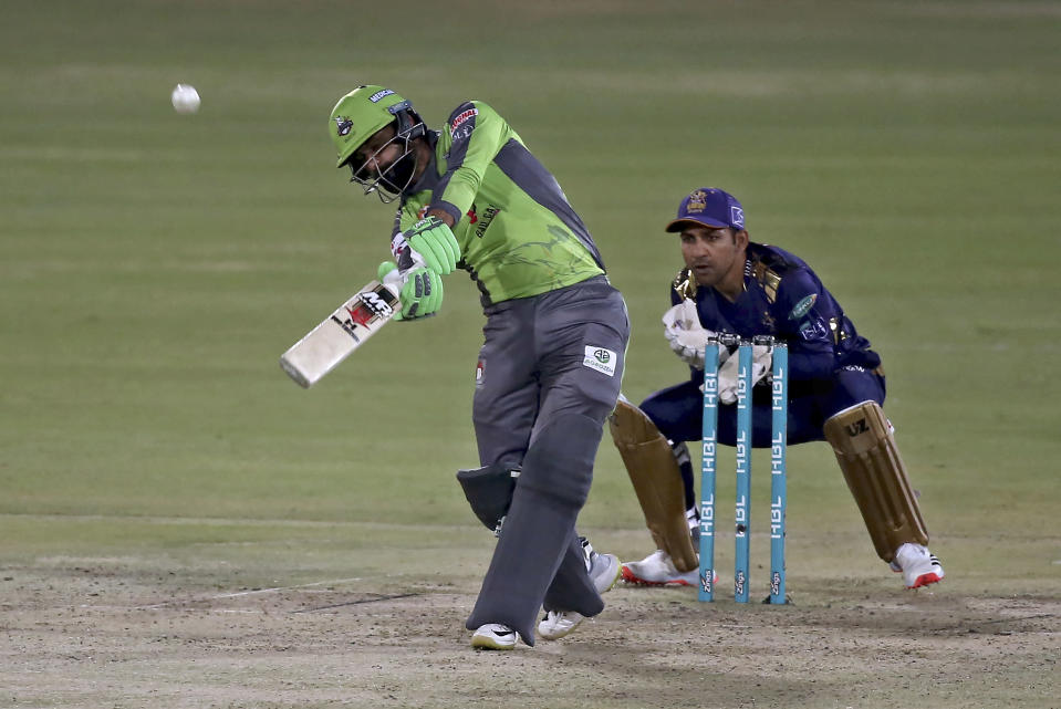 Lahore Qalandars Mohammad Hafeez, left plays a shot while Quetta Gladiators Sarfraz Ahmed watches during a Pakistan Super League T20 cricket match between Lahore Qalandars and Quetta Gladiators at the National Stadium, in Karachi, Pakistan, Monday, Feb. 22, 2021. (AP Photo/Fareed Khan)