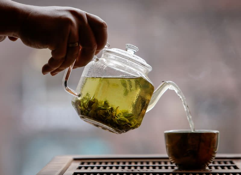 The owner of a tea house pours a cup of tea in this picture illustration