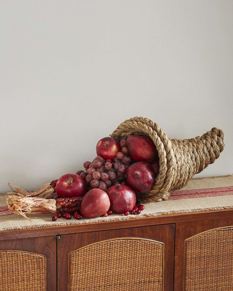 """<p>Fashion a DIY cornucopia out of just 2 materials, rope and hot glue. For a striking display fill with monochromatic bounty such as red grapes and apples, and pomegranates.</p><p><strong>To make:</strong> Fold the end of a long length of 3/4-inch manila or jute rope over on itself about 4 inches. Start wrapping the long length of rope around the folded piece, forming the cornucopia, arching it and making it wider as you work, holding everything together with hot glue. When you get to the desired size, do one last pass between and on top of the last two rows then add a circle of rope on the bottom to act as a base and keep it from rolling.</p><p><a class=""""link rapid-noclick-resp"""" href=""""https://www.amazon.com/Twisted-Manila-Rope-Hemp-Landscaping/dp/B01J07102A/ref=sr_1_13?linkCode=ogi&tag=syn-yahoo-20&ascsubtag=%5Bartid%7C10050.g.2063%5Bsrc%7Cyahoo-us"""" rel=""""nofollow noopener"""" target=""""_blank"""" data-ylk=""""slk:SHOP ROPE"""">SHOP ROPE</a></p>"""