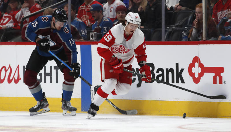 Detroit Red Wings left wing Tyler Bertuzzi, right, regains control of the puck as Colorado Avalanche right wing Valeri Nichushkin pursues in the first period of an NHL hockey game Monday, Jan. 20, 2020, in Denver. (AP Photo/David Zalubowski)