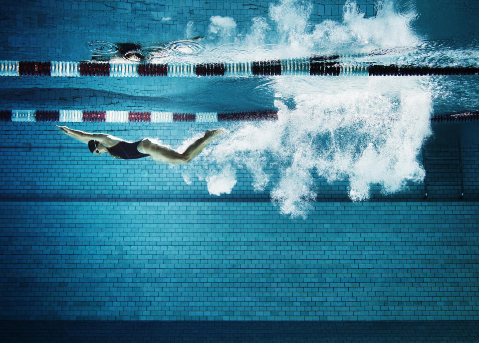 Underwater view of adult female swimmer having broken the water surface with dive