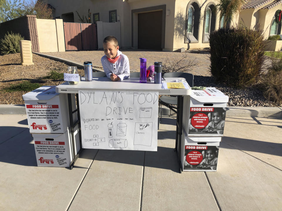 Dylan Pfeifer sits on the corner of his neighborhood cul da sac in Chandler, Ariz., Saturday, Dec. 5, 2020. Pfeifer received 555 cans and boxes and about $500 in monetary donations. (Erin Pfeifer via AP)