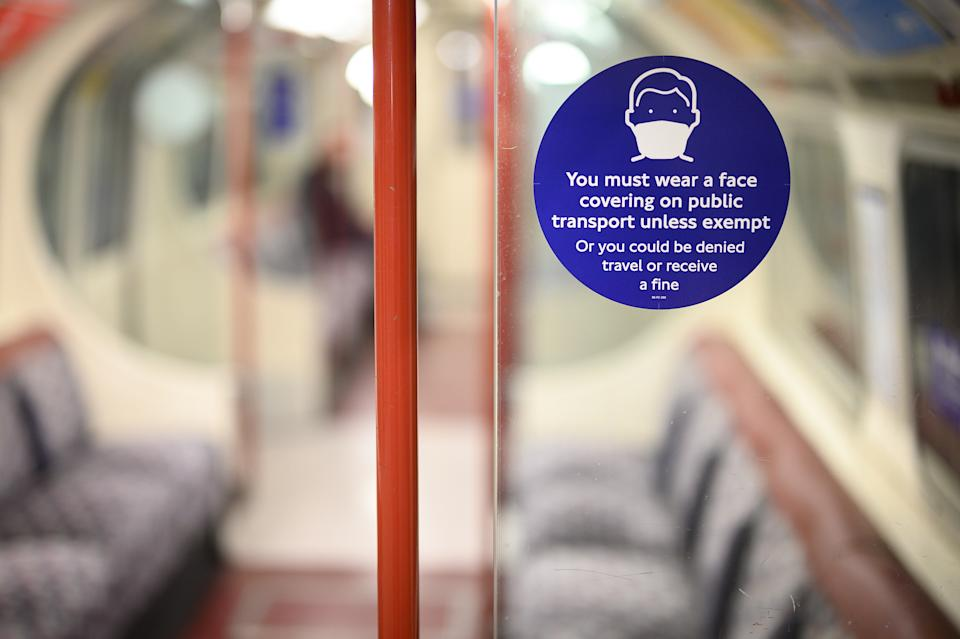 LONDON, ENGLAND - MARCH 26: A sign stating that face masks must be worn is seen inside a near-empty underground train carriage on March 26, 2021 in London, England. A year after the first Covid-19 lockdown discouraged use of public transit, ridership on the London Underground, which recorded around 4 million rides every weekday pre-pandemic, is hovering around 20 percent of normal. Transport for London worries it will take two years before ridership - and hopefully the agency's finances - returns to normal. (Photo by Leon Neal/Getty Images)