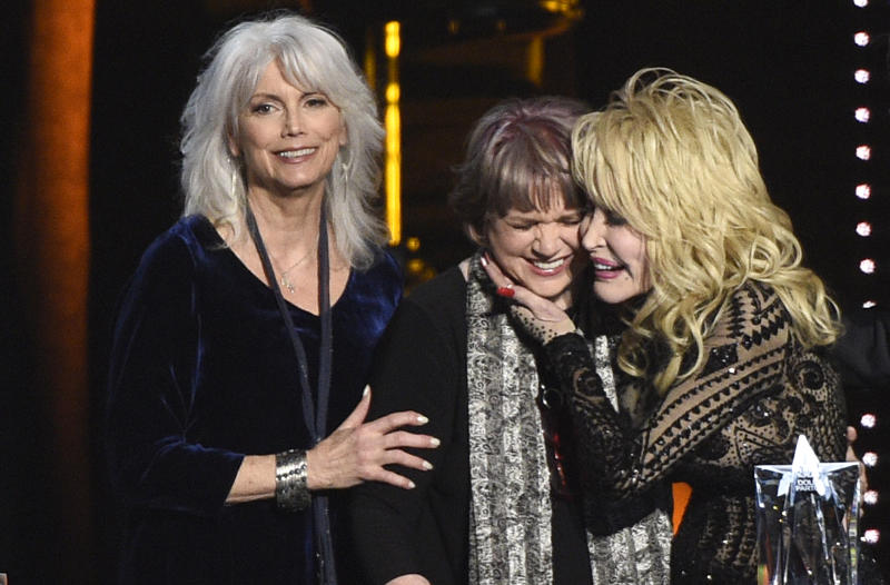 CORRECTS YEAR TO 2019 - Emmylou Harris, from left, and Linda Ronstadt present Dolly Parton with the MusiCares Person of the Year award on Friday, Feb. 8, 2019, at the Los Angeles Convention Center. (Photo by Chris Pizzello/Invision/AP)