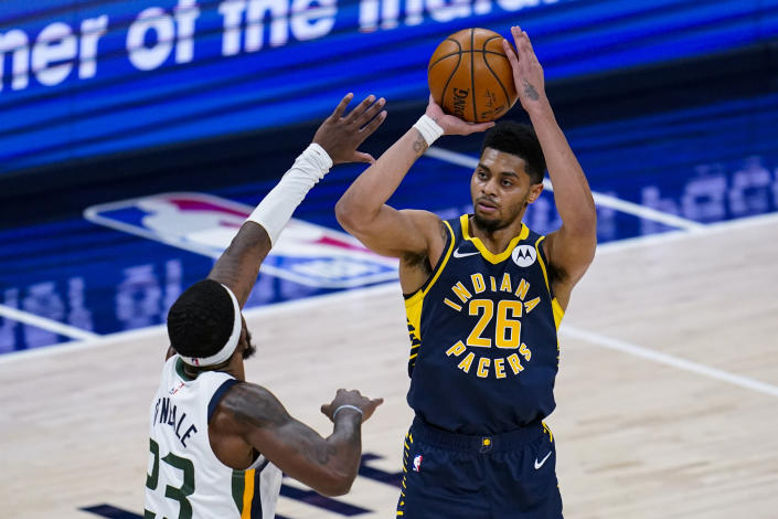 Indiana Pacers guard Jeremy Lamb (26) shoots over Utah Jazz forward Royce O'Neale (23) during the second half of an NBA basketball game in Indianapolis, Sunday, Feb. 7, 2021. (AP Photo/Michael Conroy)