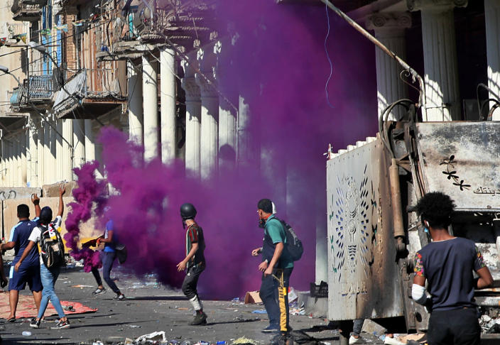 Iraqi riot police fire smoke bombs to disperse anti-government protesters during ongoing protests in the al-Rasheed street in Baghdad, Iraq, Friday, Nov. 8, 2019. The demonstrators complain of widespread corruption, lack of job opportunities and poor basic services, including regular power cuts despite Iraq's vast oil reserves. They have snubbed limited economic reforms proposed by the government, calling for it to resign. (AP Photo/Khalid Mohammed)